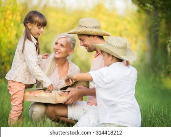 Happy parents with two kids  picking peaches in the garden