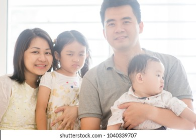Happy parents and unhappy expression daughter. Asian family spending quality time at home, natural living lifestyle indoors.
