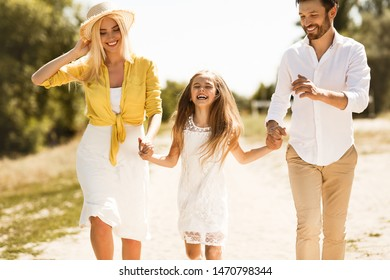 Happy parents walking with daughter, holding hands and spending time together in countryside
