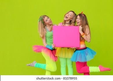 happy party teen girls in neon fancy dress clothing with blank board