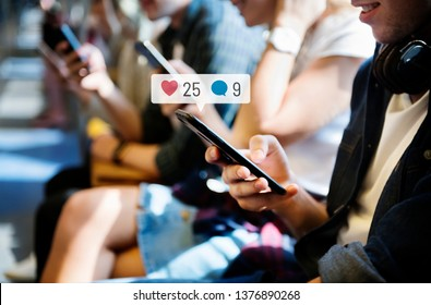 Happy passengers on a subway using social media on their smartphones