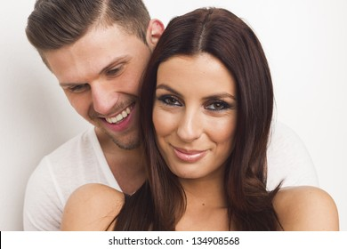Happy passionate heterosexual couple embracing by white isolated background