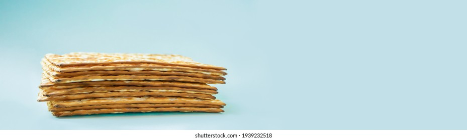 Happy Passover banner. Matzo on blue background. Traditional Jewish food for Pesach. Copy space.