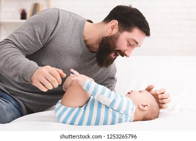 Happy paternity leave. Daddy playing with his baby son, tickling him on bed at home