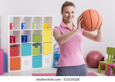 Happy PE teacher with basketball at colorful classroom