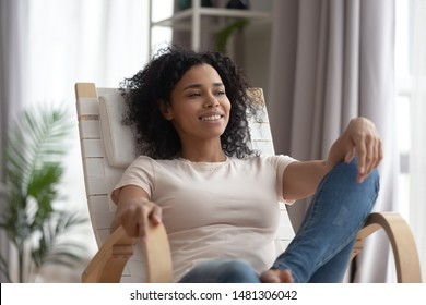 Happy peaceful african American millennial girl sit on chair relaxing at home or hotel dreaming or visualizing, smiling black young woman rest in rocker in living room look in distance thinking