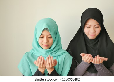 happy peaceful muslim women ramadan praying, islamic women meditating; muslim girls meditation; faithful asian muslim women with faith praying; islamic religion, islam ritual, islamic ramadan concept