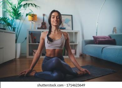 Feliz y pacífica mujer practicando yoga en casa sentada en una alfombra de yoga en la cara de vaca, José Gomukasana, estirando el cuerpo, mujer deportiva trabajando en interiores