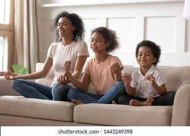 Happy peaceful young african American mom sit on couch meditate together with little children, smiling calm black mother or nanny relax practice yoga with mudra hands teach small boy and girl kids