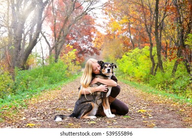 A happy and peaceful young woman is hugging her German Shepherd mix breed dog, as the rest while on a walk in the woods on a fall day.