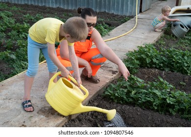 Happy peasant boy in bright T-shirt spraying plants from yellow watering can. Children help the mother to work on her home plot. Warm earth, soil, watering works. There is space for text