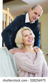 Happy pensioner sitting on sofa, husband massaging her neck at home