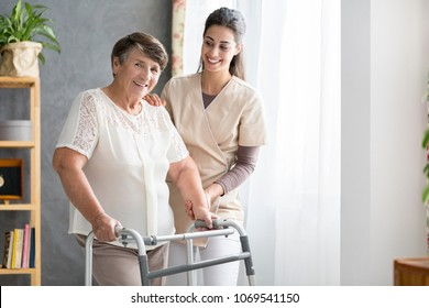 Happy pensioner trying to walk in a senior home with support of the nurse