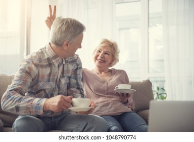 Happy pensioners having fun while sitting with comfort and holding cups with beverage. Woman is showing two fingers beside man head and laughing