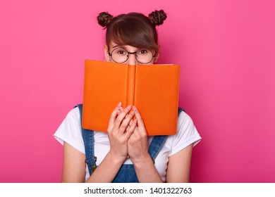 Happy pensive girl standing isolated over pink background in studio, holding orange notebook, covering half of face, looking attentively at camera, having bunches, wearing casual trendy clothes.
