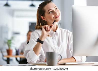 Happy pensive young businesswoman dressed in shirt sitting at her workplace at the office