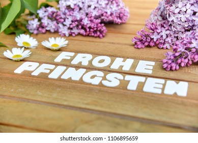Happy Pentecost Words on a wooden board with lilac bouquet