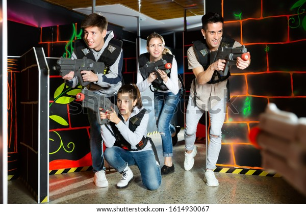 Happy people aiming laser guns at other players during lasertag game in dark room
