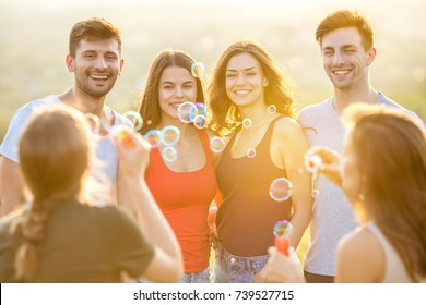 The happy people blow bubbles on the sunny background