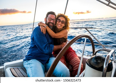 Happy people caucasian adult couple enjoy the sail boat trip on summer holiday vacation - outdoor leisure activity with ocean and sunset in. background - sailing with love and romance