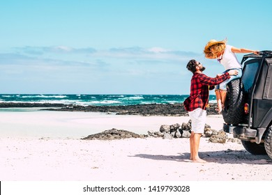 Happy people couple on summer holiday vacation - woman sitting on a big off road car and man standing down touching her - love and relationship concept in outdoor scenic beautiful place