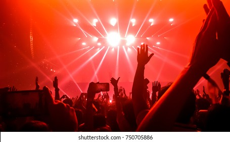 Happy people dance in nightclub party concert and listen to music from DJ on the stage in background. Cheerful crowd celebrate Christmas and New Year party 2019. Young people lifestyle and nightlife.