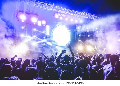 Happy people dancing and having fun in new year's eve festival party outdoor - Crowd of millennial guys celebrating concert event - Soft focus on center man head with hands up - Fun and youth concept