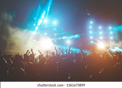 Happy people dancing and having fun in summer music festival party outdoor - Crowd of millennial guys celebrating concert event - Soft focus on center hand up with blue flare - Fun and youth concept