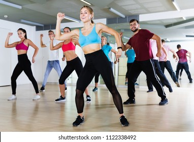 Happy people of different ages studying zumba dance elements in dancing hall