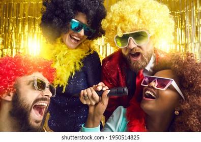 Happy people dressed in funny fancy costumes having fun at music show or karaoke disco party. Group of male and female friends with mikes singing, shouting and dancing on stage with gold background