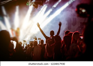 Happy people enjoying rock concert, raised up hands and clapping of pleasure, active night life concept.
