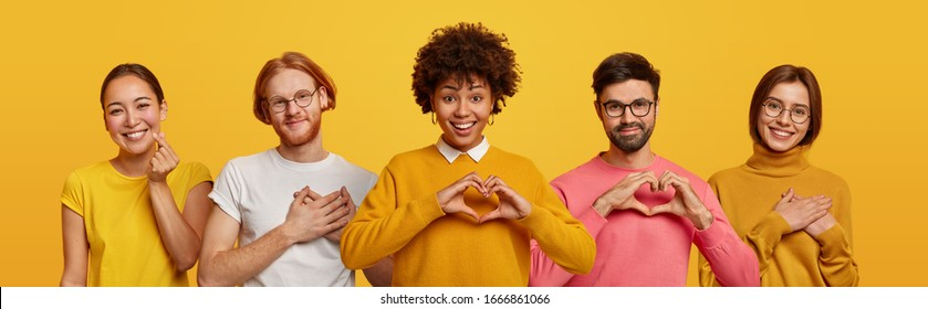 Happy people express love and gratitude, shape hearts to camera, confess in good feelings, woman and man touched by heartwarming words. Group of diverse men and women pose over yellow studio wall
