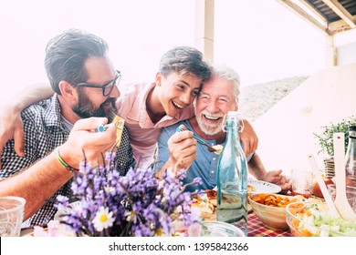 Happy people family concept laugh and have fun together with three different generations ages : grandfather father and young teenager son all together eating at lunch