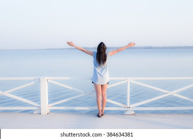 Happy people - free woman enjoying nature near river. Freedom and serenity concept with female model in ecstatic enjoyment.