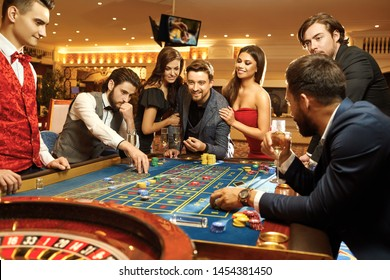Happy people gambling poker roulette in casino