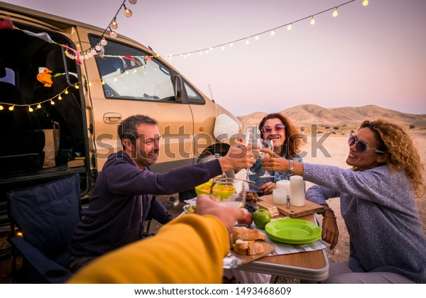 Happy people group of friends toasting and enjoying the travel vacation together - cheerful. womanandman with food in outdoor leisure activity - modern van and ocean in background