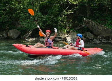 Happy people having adventure on mountain river. Rafting in small boats