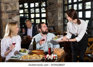 Happy people having dinner at rural restaurant and drinking wine. High quality photo