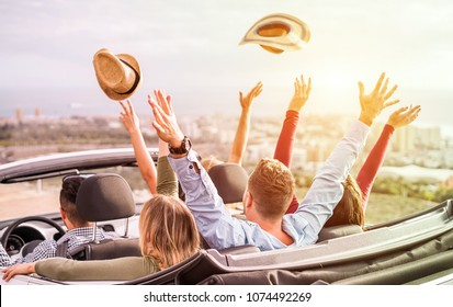 Happy people having fun in convertible car in summer vacation - Young tourist friends traveling in cabriolet auto - Radial purple and green filters editing - Main focus on left blond girl head