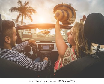 Happy people having fun in convertible car in summer vacation - Young friends laughing on cabrio auto outdoor - Main focus on girl face - Travel, youth lifestyle, holidays and friendship concept