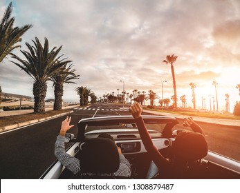 Happy people having fun in convertible car in summer vacation at sunset - Young couple enjoyng  holiday on cabrio auto outdoor - Travel, youth lifestyle and wanderlust concept - Focus on hands
