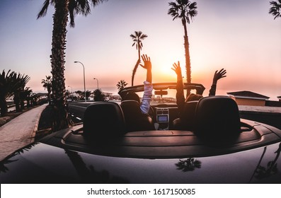 Happy people having fun in convertible car in summer vacation at sunset - Young couple enjoyng  holiday on cabriolet auto outdoor - Travel, youth lifestyle and wanderlust concept - Focus on hands
