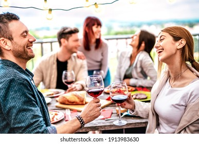 Happy people having fun drinking wine on terrace at private dinner party - Young friends eating barbeque food at restaurant together - Dinning lifestyle concept on warm filter - Focus on right glass