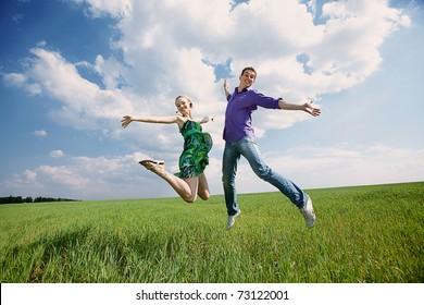 Happy people is jumping in field