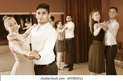 Happy  people learning to dance waltz in dancing class