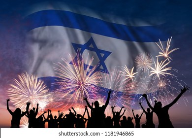 Happy people are looking holiday fireworks with flag of Israel in sky, independence day