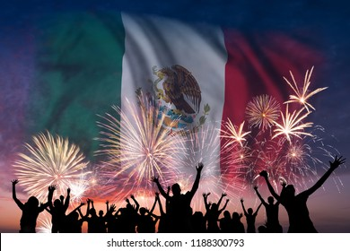 Happy people are looking holiday fireworks with flag of Mexico in sky, independence day