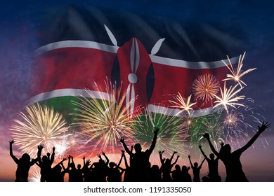 Happy people are looking holiday fireworks with flag of Kenya in sky, independence day