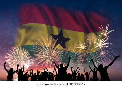 Happy people are looking holiday fireworks with flag of Ghana in sky, independence day
