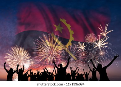 Happy people are looking holiday fireworks with flag of Angola in sky, independence day
